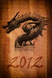 Dragon statue on the wood texture for 2012. Image of Dragon Statue on the vintage wood texture background Stock Images