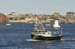 Dragon vert de bateau de homard avec le phare et de bord de mer le dos dedans photographie stock