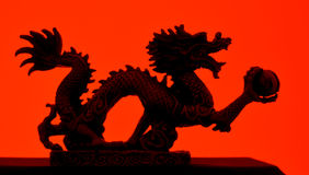 Dragon. This dragon was shot in the studio. Red gel lighting fills the background. The silhouette effect is light enough to show the details on the dragon. Shot royalty free stock photography