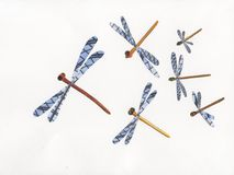 Dragonflies out of paper, pattern. Dragonflies out of paper, multiple objects on white background, construction paper, composite image, image montage Royalty Free Illustration