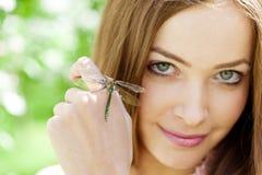 dragonfly смотрит на ее женщину Стоковая Фотография