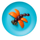 Dragonfly made of orange. And grape on plate royalty free stock photography