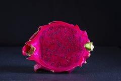 Dragonfruit rose exotique coupé sur le fond noir Haut étroit de fruit du dragon Fruit rouge mûr de pitahaya avec la moitié Fruit  Images stock
