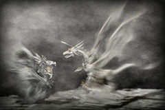 Dragons Attack. Close-up of pewter figures of two dragons in a confrontational pose.  Zoomed for an appearance of motion.  Mist added for atmosphere.  Vignetted Stock Images