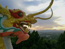 Dragons breathing fire. Golden Dragon spewing flames are among the blue sky Stock Photos