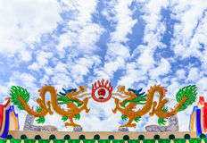 Dragons on the roof of a Chinese shrine. With stripe cloud and blue sky Stock Photos