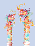 Dragons. Two replicas of Chinese dragon spiralling over  long poles Royalty Free Stock Photo