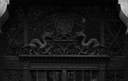Dragons watching. Shot in black and white. Placed on the main door of this historic building, sculpture  representing a couple of dragons. Set in Eixample Stock Images