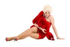 Dragqueen im roten Kleid mit dem Pelz, der auf dem Boden liegt Lizenzfreies Stockfoto