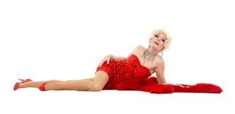 Dragqueen im roten Kleid mit dem Pelz, der auf dem Boden liegt Stockfoto
