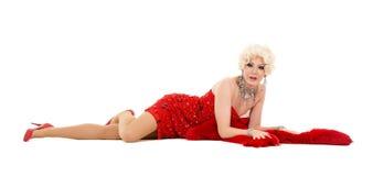 Dragqueen im roten Kleid mit dem Pelz, der auf dem Boden liegt Lizenzfreie Stockbilder
