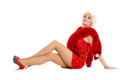 Dragqueen im roten Kleid mit dem Pelz, der auf dem Boden liegt Lizenzfreie Stockfotos