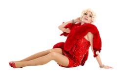 Dragqueen im roten Kleid mit dem Pelz, der auf dem Boden liegt Stockfotografie