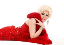 Dragqueen im roten Kleid mit dem Pelz, der auf dem Boden liegt Stockfotos