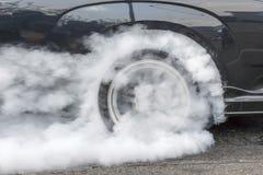 Dragracingauto brennt Gummi weg von seinen Reifen Lizenzfreie Stockbilder