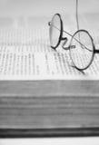 Draht eingefaßte Gläser auf einem Buch Lizenzfreies Stockbild