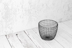 Drahtkorb auf weißem Boden Stockfotos