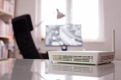 Drahtloser Router auf reflektierender Oberfläche, inneres kleines Büro Stockfotos