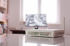 Drahtloser Router auf reflektierender Tabelle, mit aus Fokusmonitor heraus Lizenzfreie Stockbilder