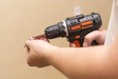 Drahtloser Schraubenzieher in den Händen eines Mannes, das Thema der Reparaturarbeit Lizenzfreies Stockbild