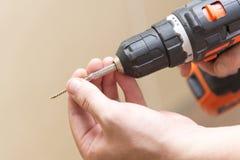 Drahtloser Schraubenzieher in den Händen eines Mannes, das Thema der Reparaturarbeit Stockfotos