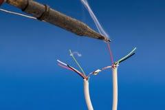 Drahtloses Löten mit Zinn auf blauem Hintergrund Lizenzfreies Stockfoto