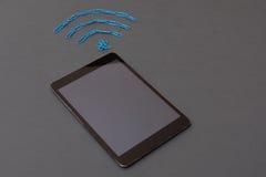 Drahtloses Signalsymbol gemacht von den Papierklammern und von der digitalen Tablette Stockfotografie