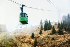 Drahtseilbahn absteigendes thorugh der Nebel von der Spitze Lizenzfreie Stockfotos