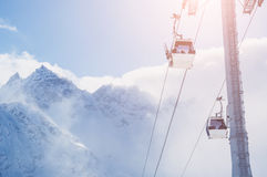 Drahtseilbahn auf dem Skiort und den schneebedeckten Bergen Lizenzfreie Stockfotografie