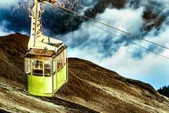 Drahtseilbahn, die oben über den Berg und die Wolken hinausgeht Lizenzfreies Stockbild