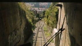 Drahtseilbahn, die sich nach unten, Passagiere transportierend, um zu stationieren, durch Fenster ansehen bewegt stock footage