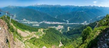 Drahtseilbahn im Berg Ansicht über die Wohnhäuser des grünen Tales, umgeben durch Hochgebirge nave lizenzfreie stockfotos