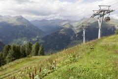 Drahtseilbahn mit Ansicht von Alpen im Hintergrund. Stockfoto