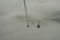 Drahtseilbahnen reisten in den Nebel Lizenzfreie Stockbilder