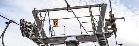 Drahtseile über dreht sich in Mechanismus auf Skisesselliftstützspalte, Nr. 6 auf gelber Platte, heller Himmel stockfoto