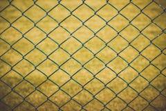 Drahtzaun mit gelbem Gras auf Hintergrund lizenzfreie stockfotos