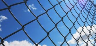 Drahtzaun mit weißen Wolken und Hintergrund des blauen Himmels Stockfotos
