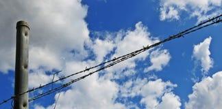 Drahtzaun mit weißen Wolken und Hintergrund des blauen Himmels Stockbilder