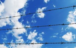 Drahtzaun mit weißen Wolken und Hintergrund des blauen Himmels Lizenzfreie Stockfotografie