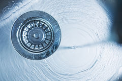 Drain. Water flowing in a spiral down a stainless steel drain Royalty Free Stock Photos