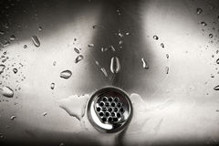 Drain. Water going down the drain in stainless steel sink stock image