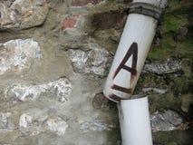 Drain cassé avec la lettre A là-dessus avant un mur en pierre images stock