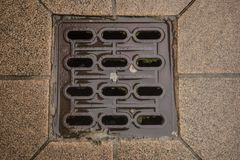 Drain cover in the middle of a road Stock Photos