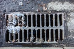 Drain grate with the garbage. On it royalty free stock photos