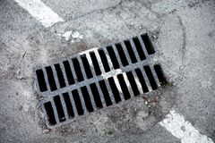 Drain grate with road marking line on it Royalty Free Stock Images