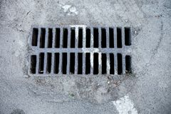Drain grate with road marking line on it Royalty Free Stock Photography