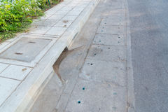 Drain gutter in the road, next to pavement Royalty Free Stock Photo