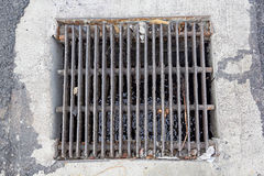 Drain gutter in the road, next to pavement, showing curb. Stock Photo