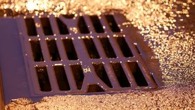 Drain metal grill on the road during the rain. Pig-iron rusty iron hatch