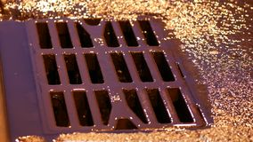 Drain metal grill on the road during the rain. Pig-iron rusty iron hatch plate
